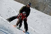 stock photo of family ski vacation  - Father teaching his young son to ski - JPG