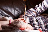 picture of ear candle  - A Mature Male having hopi ear candle treatment - JPG