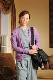 stock photo of rn  - a home health nurse arriving in scrubs and bag - JPG