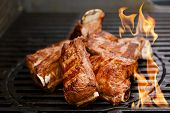 beef short ribs on bbq flame grill poster