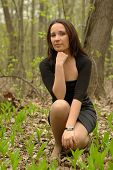 stock photo of bolero  - Girl in a little black dress sitting in the forest - JPG