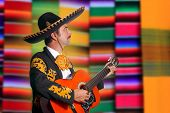 Charro Mariachi profile man playing guitar with blurred serape background