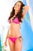 Glamour style photo of sensual young girl in pink bikini posing in summerhouse on beach.