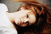 stock photo of nose piercing  - Closeup portrait of beautiful young girl lying on asphalt - JPG