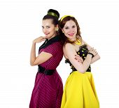 stock photo of parti poodle  - two stylish young woman in bright colour dresses - JPG