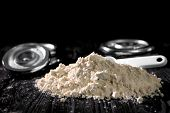 Heap of protein powder with scoop on table, closeup poster