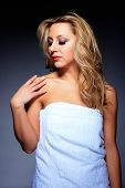 Young, healthy and beautiful woman in towel over gray background