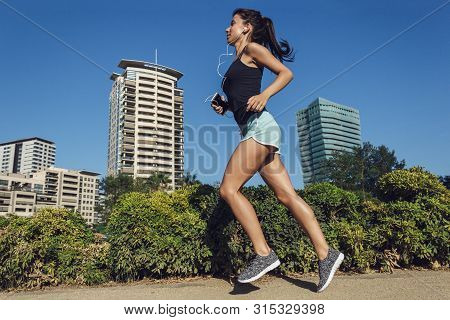 poster of Beautiful Fitness Girl Running In The City. Female Running On Sidewalk With Urban Background Of Skys