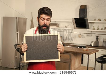 poster of Secret Tips. Useful Information. Man Bearded Hipster Red Apron Stand In Kitchen. Kitchen Furniture S