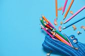 Funny Back To School Concept - Pencil Case Eating Pencils On Blue Background. Space For Text. poster