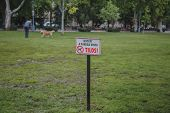 A Person Walks With A Dog In A Territory Where It Is Forbidden To Walk A Dog, A Hungarian Sign Is On poster