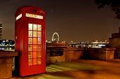 Traditional english phone booth with the London Center in the background