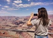 Girl Taking Photos In The Grand Canyon With Mobile Phone. poster