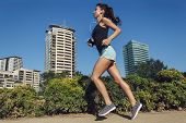 Beautiful Fitness Girl Running In The City. Female Running On Sidewalk With Urban Background Of Skys poster