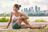Yoga stretch exercise fit Asian woman stretching lower back for spine health on city outdoor fitness poster