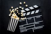 Filmmaker Profession With Clapperboard And Popcorn On Black Background Top View poster