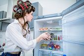 Beautiful girl is posing in everyday clothes with curlers in her hair near a fridge. Fashion home sh poster