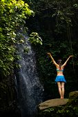 Young Traveler Woman Wearing Swimsuit At Waterfall In Tropical Forest.  Excited Caucasian Woman Rais poster