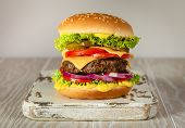 Delicious Burger With Meat, Melted Cheese, Dripping Sauce And Vegetables On White Rustic Background. poster