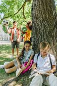 Adorable Schoolkids Sitting Under Tree And Reading Books Near Multicultural Friends poster
