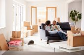 Couple Taking A Break And Sitting On Sofa Celebrating Moving Into New Home With Champagne poster