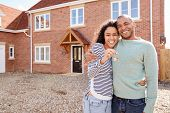 Portrait Of Couple Holding Keys Standing Outside New Home On Moving Day poster