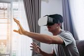 Young Asian Man Wearing Virtual Reality Glasses At Living Room For Admiring Virtual Reality. poster
