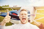 Happy Male Pilot Selfie Photo Aviator Smiling On Background Propeller Driven Aircraft. Travel Rental poster