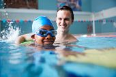 Male Swimming Coach Giving Boy Holding Float One To One Lesson In Pool poster