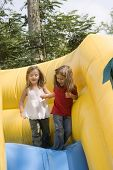 pic of inflatable slide  - Two beautiful little girls having fun on inflatable playground - JPG