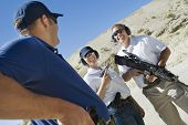 Three military people with guns at firing range
