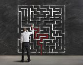 stock photo of impossible  - Businessman finding the solution of a maze - JPG