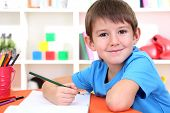 stock photo of diligent  - Cute little boy drawing in his album - JPG