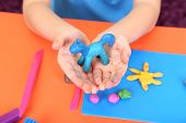Child's hands holding hand-made plasticine hourse over desk