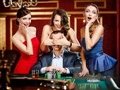 Girls cover the eyes of the gambler playing roulette at the casino