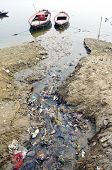 stock photo of gang  - sewage water pollution channel to holy Ganges river In Varanasi India - JPG