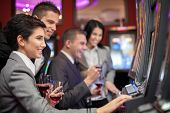 Young people enjoying to play slot machines at casino
