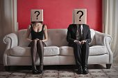 A woman and a man sitting on a sofa with a box on which is drawn a question mark over their heads