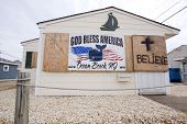 OCEAN BEACH, NJ - JAN 13: A banner that says God Bless America hangs next to a cross and word 'Belie