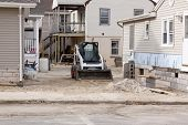 SEASIDE HEIGHTS, NJ - JAN 13: A bulldozer in-between homes on January 13, 2013 in Seaside Heights, New Jersey. Clean up continues 75 days after Hurricane Sandy struck the shore in October 2012.