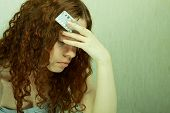 stock photo of contraception  - The girl in confusion holds contraceptive tablets in hands - JPG