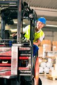 stock photo of forklift driver  - forklift driver in protective vest driving forklift at warehouse of freight forwarding company - JPG