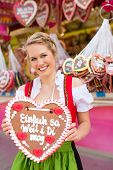 Young woman in traditional Bavarian clothes - dirndl or tracht -with a gingerbread souvenir heart on a festival or Oktoberfest