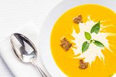 Pumpkin Soup With Basil On Served Table
