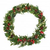 Natural christmas wreath with holly, mistletoe, ivy, pine cones and cedar leaf sprigs over white bac