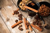 stock photo of cinnamon sticks  - A glass of hot mulled wine spices cinnamon star anise brown sugar and nuts on a wooden board - JPG