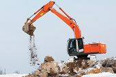 Heavy excavator loader at winter moving frozen soil works in sandpit