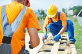 stock photo of work crew  - construction carpenters workers crew on roof installation work - JPG