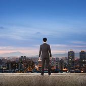 Asian business man stand and look the city under sky in the night, concept of hard work, business, f