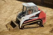 image of skid-steer  - A small tracked skid loader crosses a sandy service at a construction site